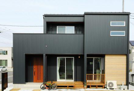 黒と木目のバランスが美しいひろびろウッドデッキのある家